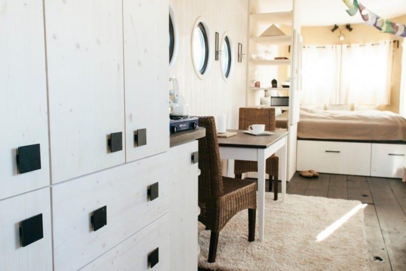 Innenraum mit Schrankwand, Esstisch und Schlafbereich