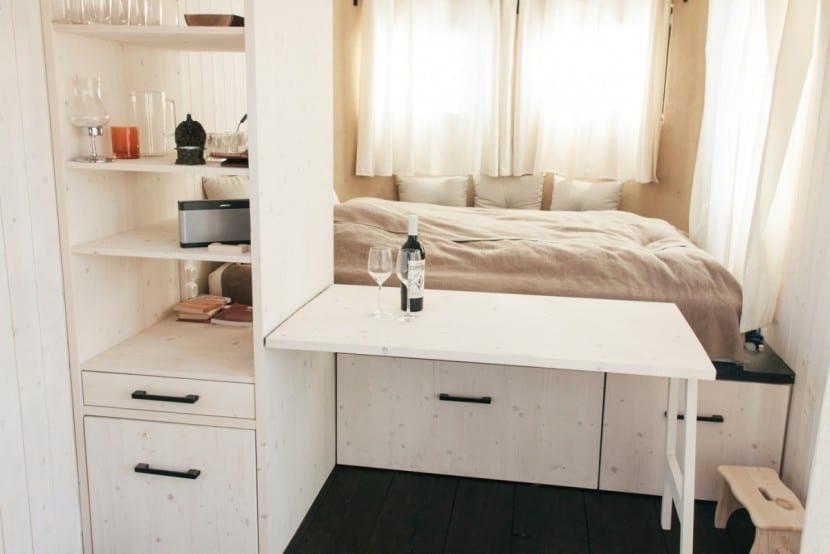 Wohnwagon innen: Klapptisch, Regal und Schlafzimmer