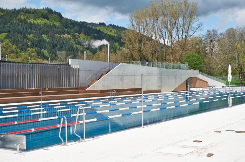 Schwimmerbecken, dahinter die Garderobengebäude mit Holzterrasse