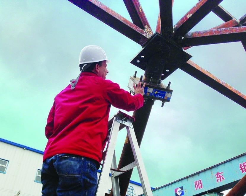 Ein Ingenieur prüft ein angeflanschtes Isokorb Element des Typs KST zur thermischen Trennung, das zur Minimierung von Wärmeverlusten an Stahlstützensystem montiert wurde, das die Commandante-Ferraz-Antarktisstation über den gefrorenen Boden hält. Foto: Afa-consult / Estúdio 41.