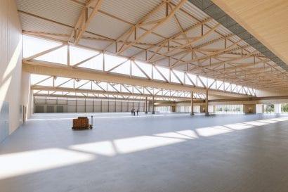 Rund 82 m lange Fachwerkträger mit nur einer Stütze überspannen als Zweifeldträger die Halle. BauBuche ermöglicht es, die Feldweiten von 40 m bzw. 42 m mit filigranen Träger-Abmessungen zu überbrücken. (Visualisierung: HK Architekten)