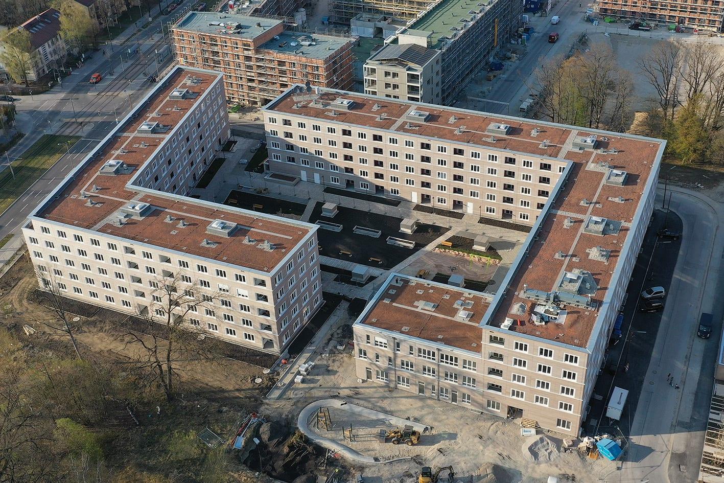 Die zwei fünfgeschossigen Mehrfamilienhäuser sind in zwei gegenüberliegenden L-Winkeln angeordnet. Es wurden 181 Wohnungen für 1-8 Personen geschaffen. Im Erdgeschoss des dreistöckigen Gebäudeteils sind eine Kindertagesstätte und ein Gemeinschaftsraum untergebracht. (Foto: GEWOFAG / Frank De Gasperi)